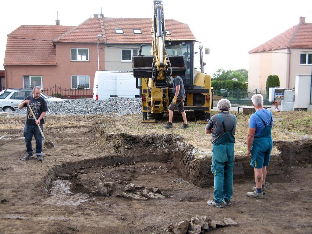 Začala skrývka zeminy, bagr odkryl jedno z míst, kde se nachází hrob. Byl označen - H 1